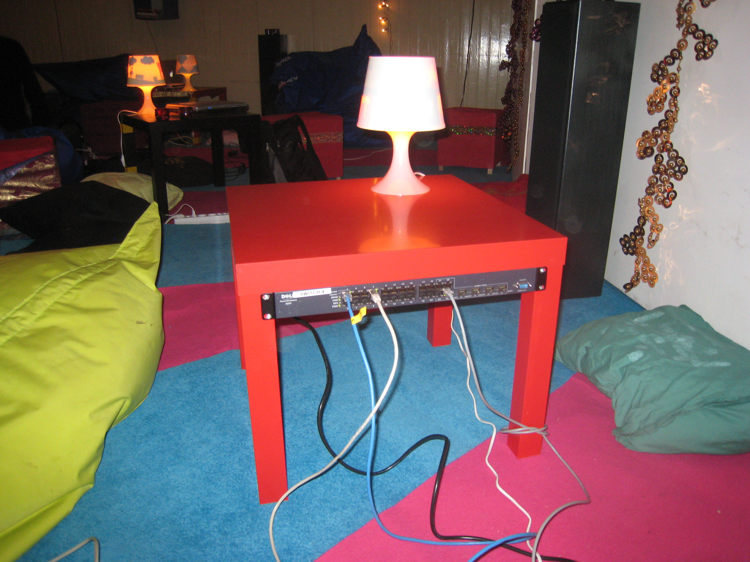 A red LACK side-table with a small white lamp sitting on top of it and a network switch mounted to the underside.
